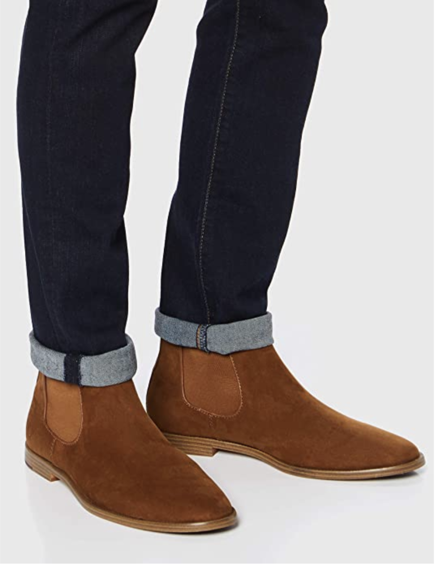 A model in a pair of camel ankle height chelsea boots