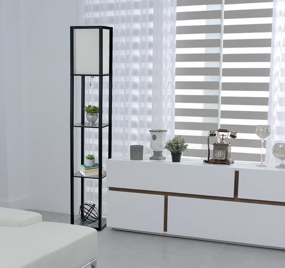 Black box lamp with lamp shade at top and three shelves underneath