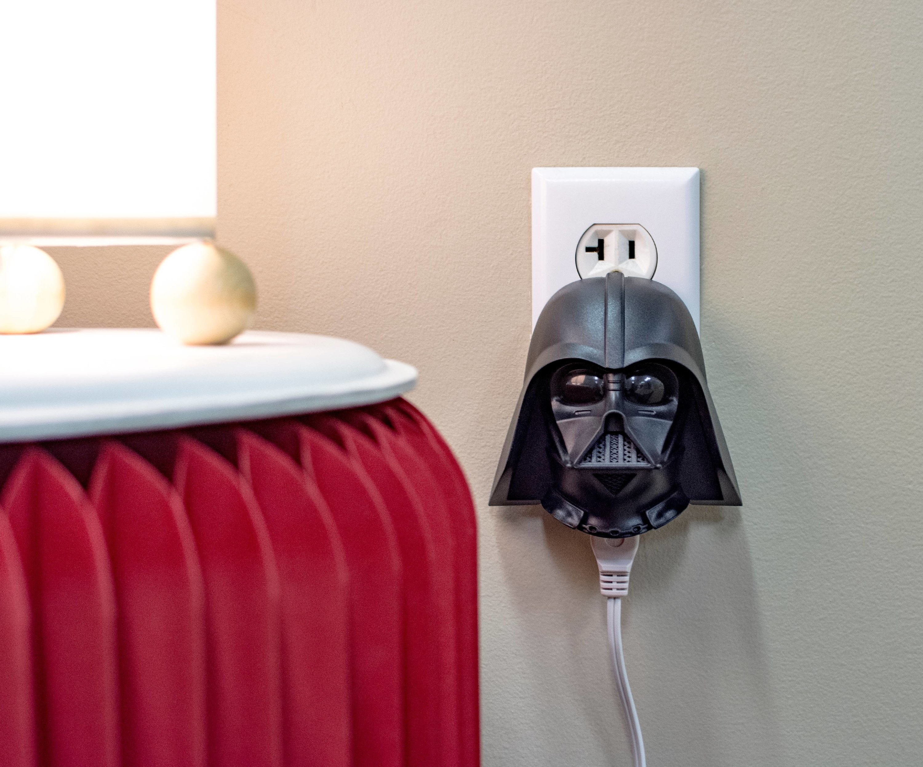 darth vadar face plugged into the wall with a lap plugged into it
