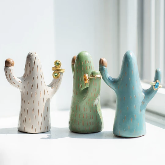 three saguaro cacti figures with two arms to hold rings