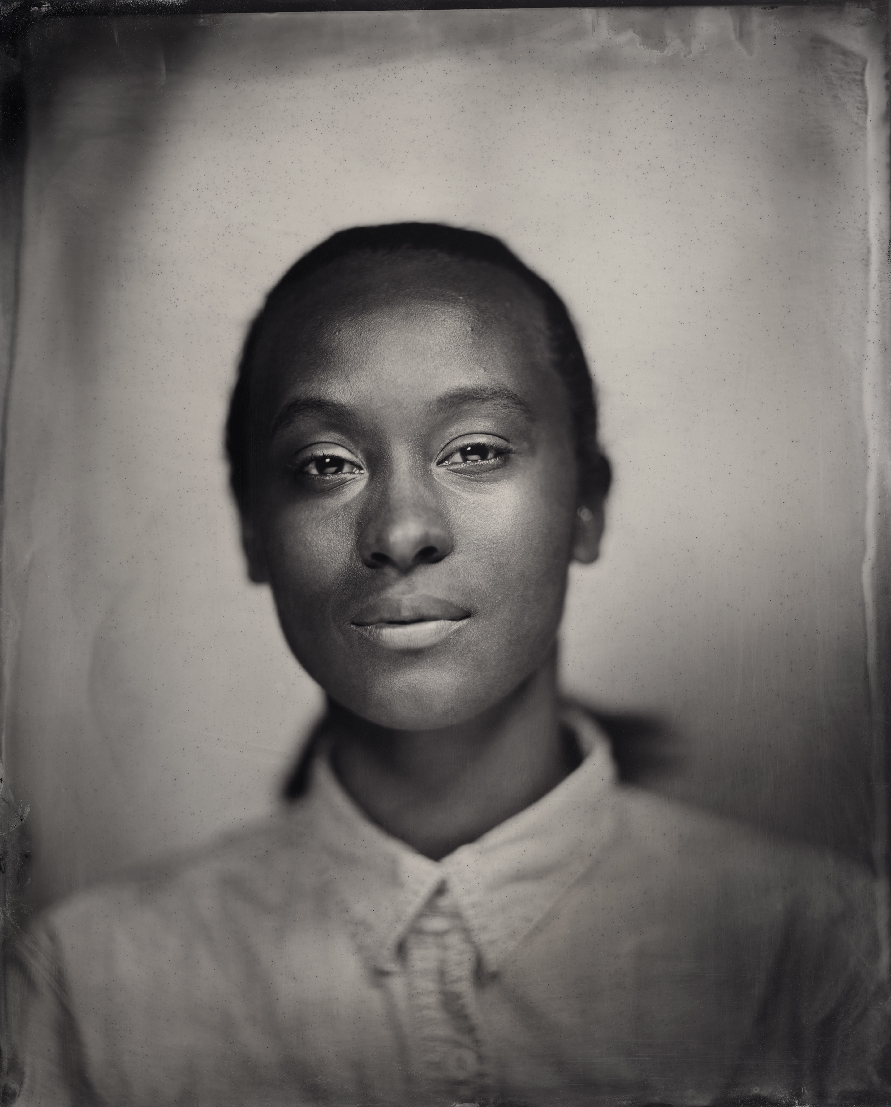 A tin type portrait of a young BIPOC woman in a collared shirt looking directly at the camera.