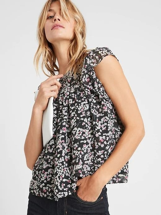 person wearing a black floral blouse