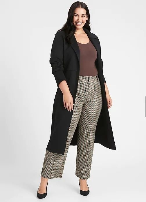 person wearing relaxed high waisted pants in a brown plaid design
