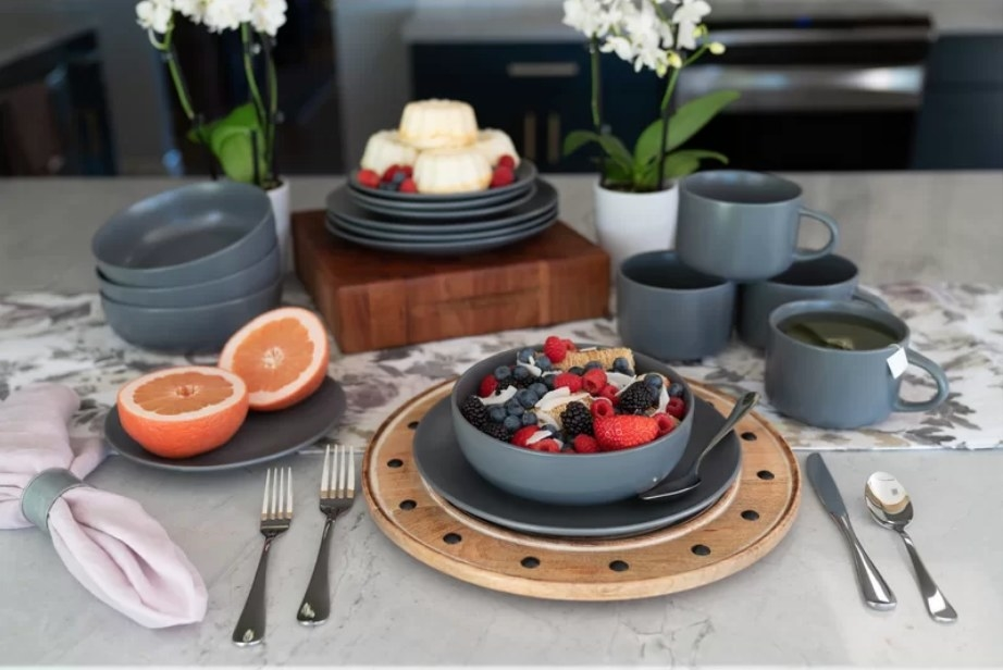 Breakfast served on black plate set with matching bowls and mugs