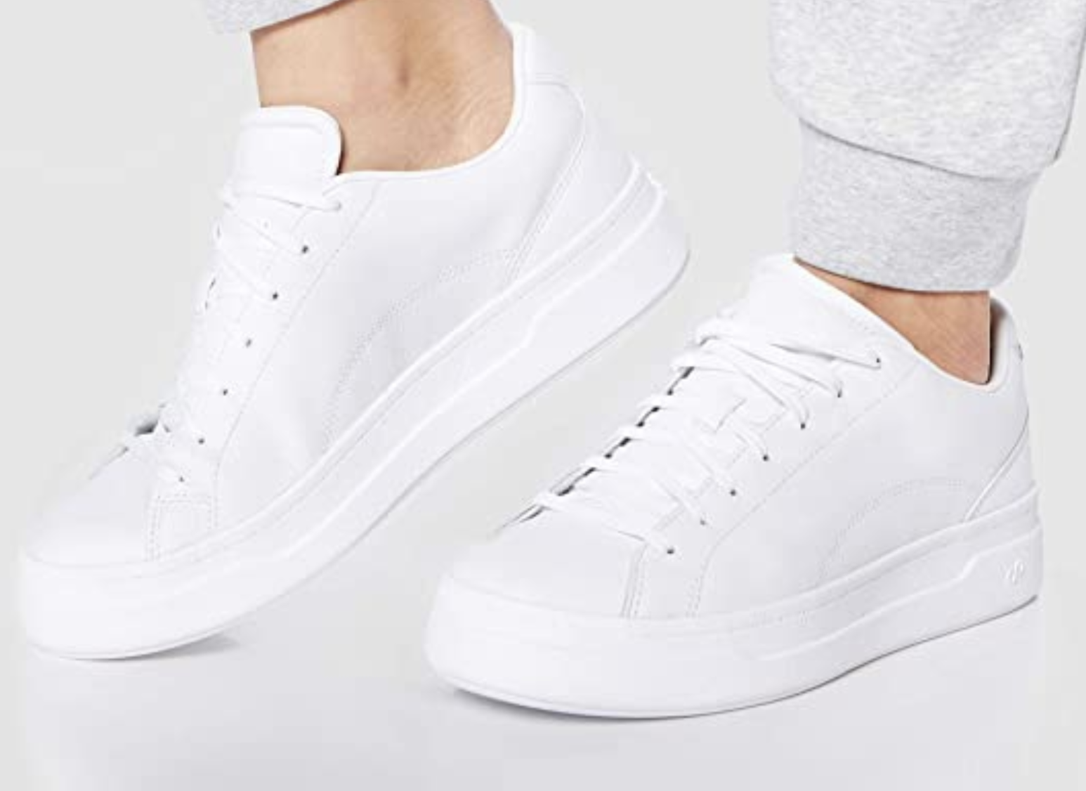 A model in the white lace up sneakers