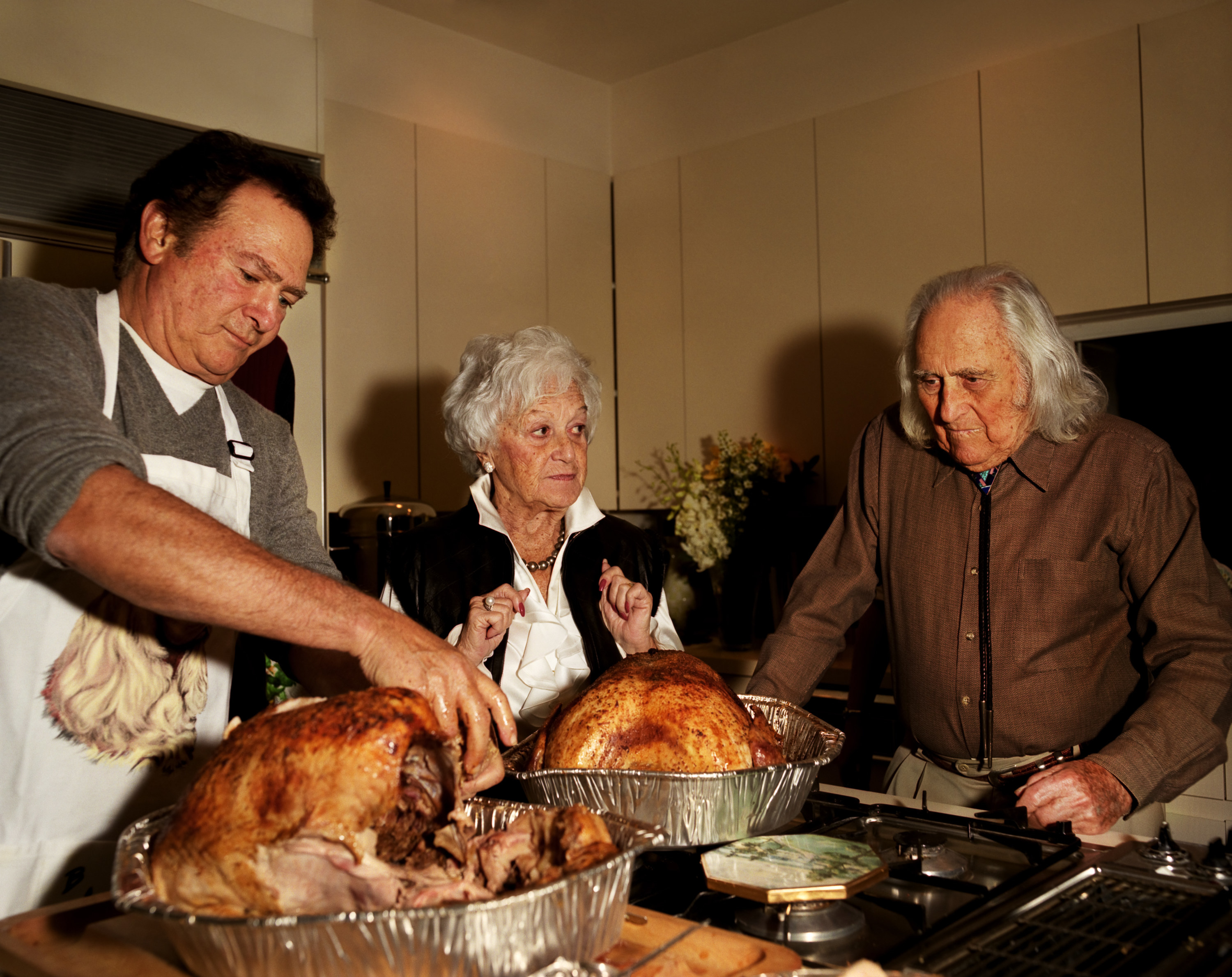 A man, an older woman, and an older man with two turkeys in front of them