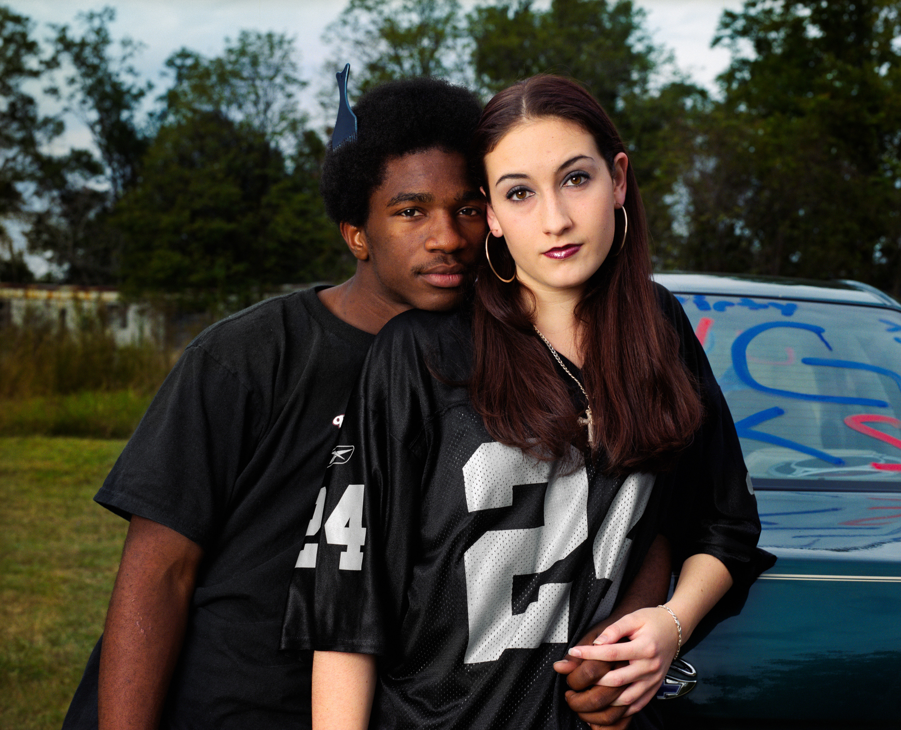 A black teenager with an afro and his arm around a white girl in a football jersey