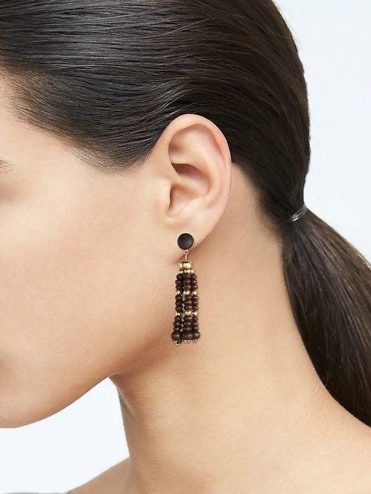 person wearing a brown bead drop earring