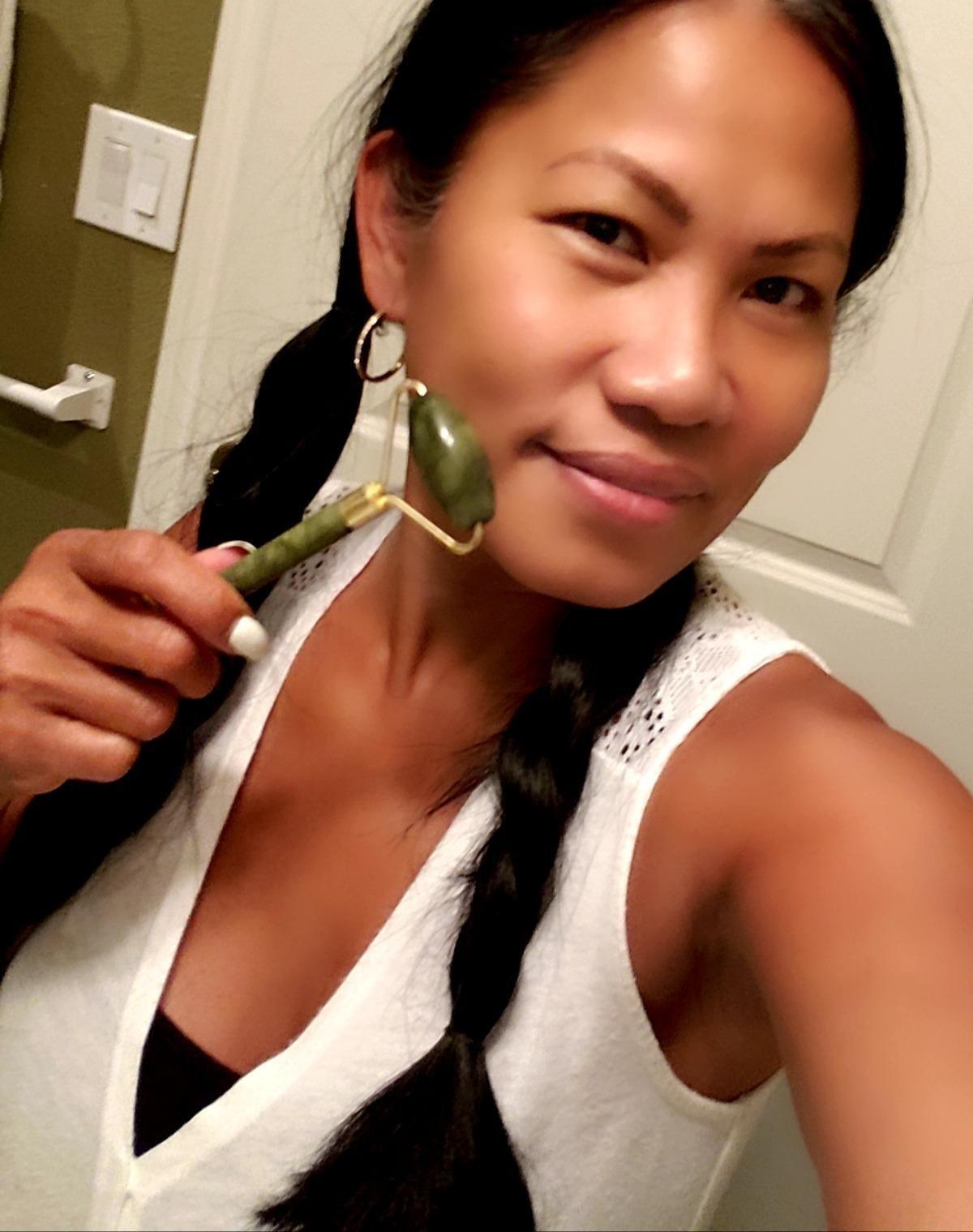 Reviewer uses dark green jade roller on their cheek