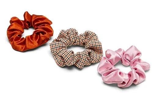 orange scrunchie, houndstooth scrunchie, and a pink scrunchie