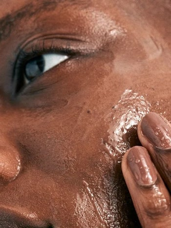Model applies Glossier's clear Milky Jelly Cleanser on their face