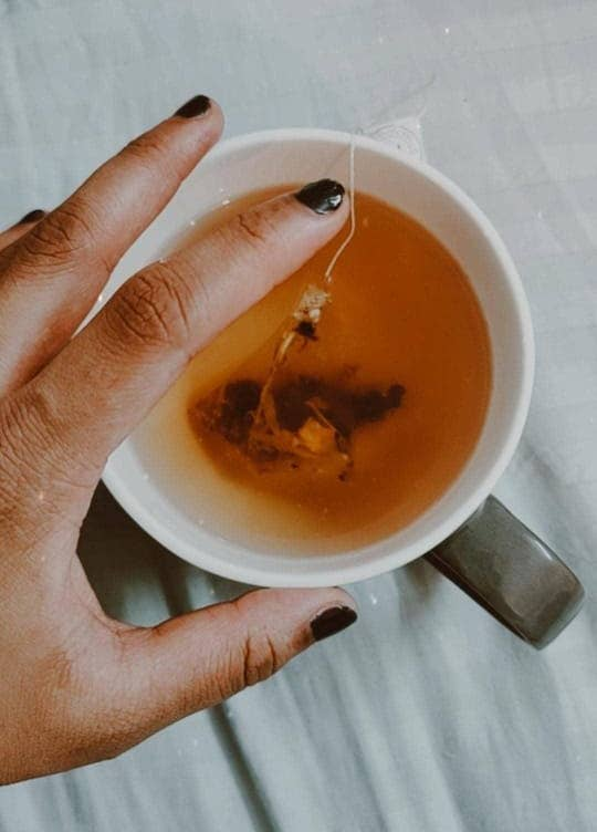 A hand over a cup of tea with the tea bag inside.