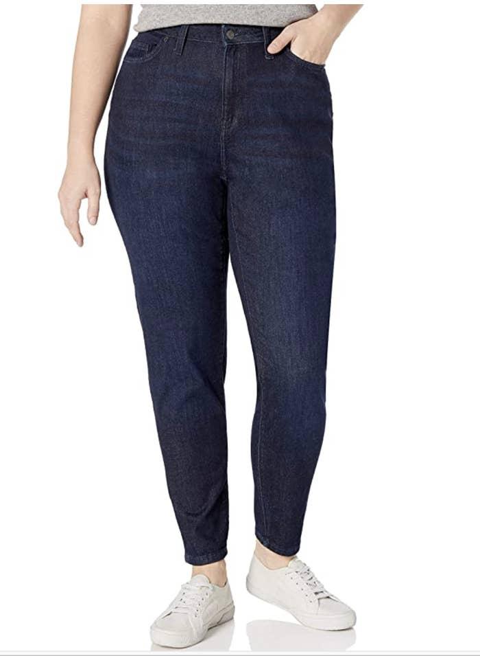 Model in a pair of high waisted, dark denim skinny jeans