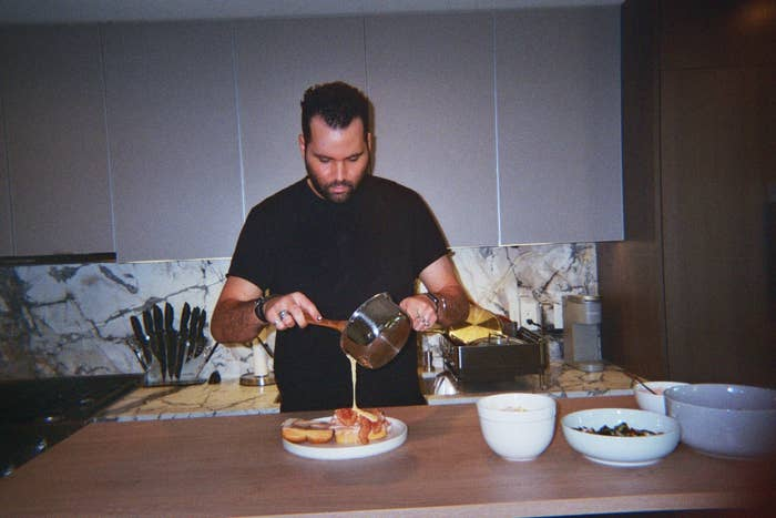 Jeremy pours a sauce on top of a meal in his kitchen