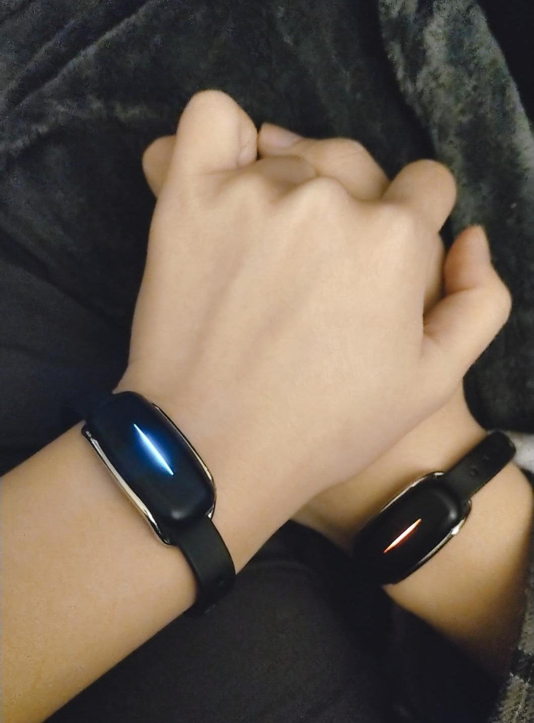 Two hands holding wearing the bluetooth friendship bracelets
