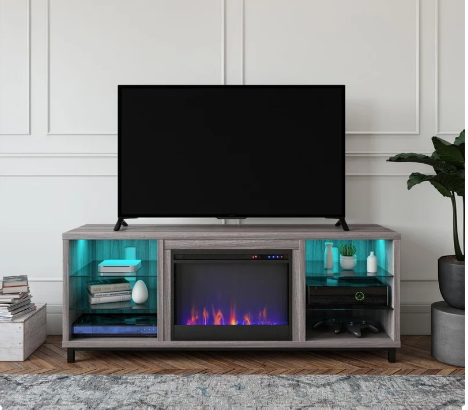 TV stand with electric fire place in the middle and two shelves on either side with LED lighting