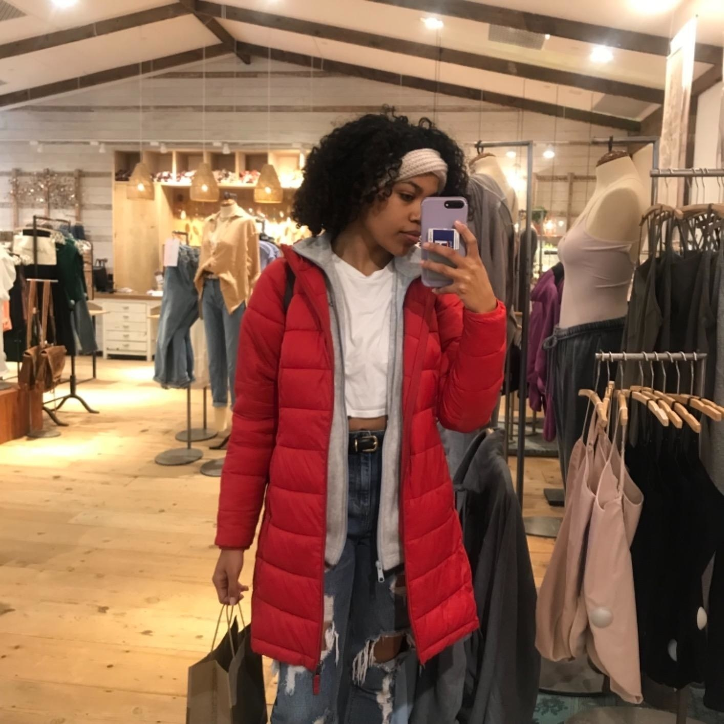 Reviewer wearing the knee-length quilted puffer in red