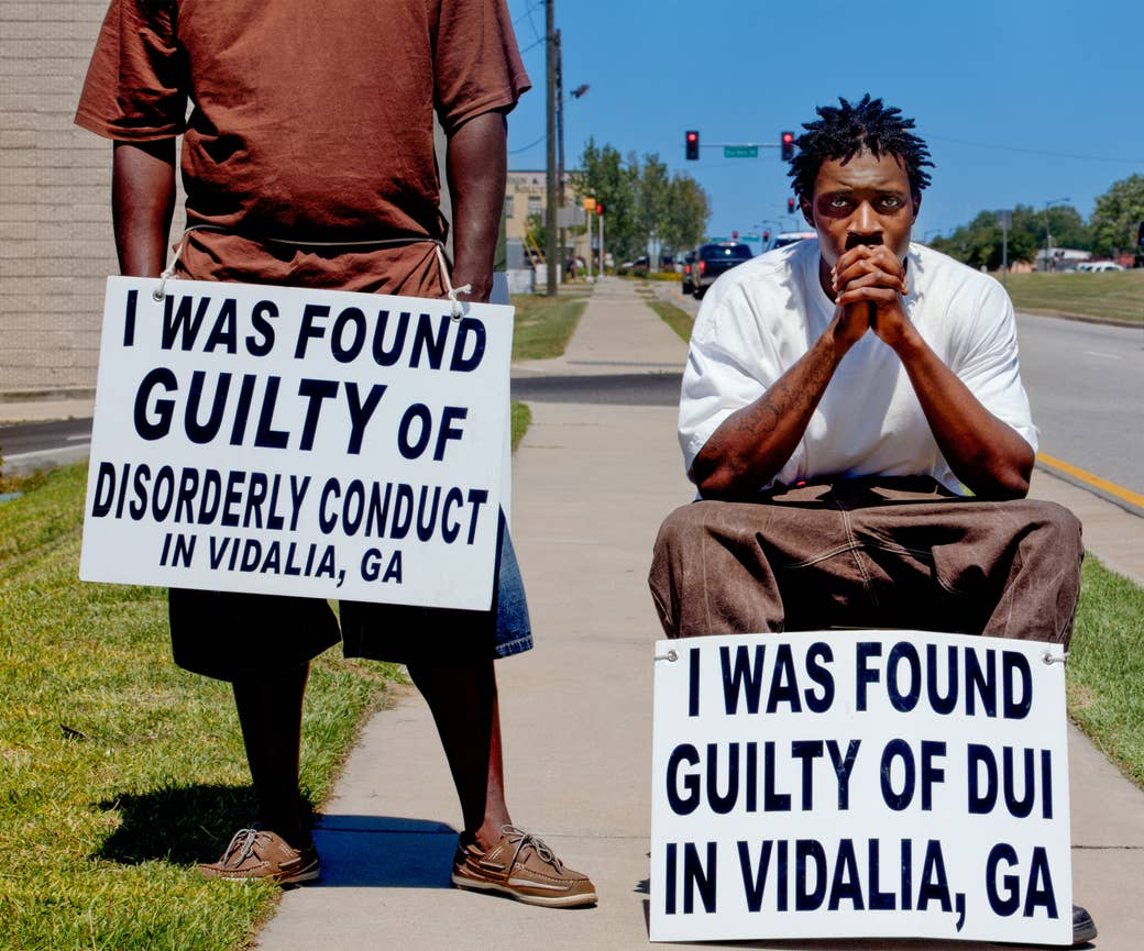 Two black men with signs around their waists on a sidewalk next to a road