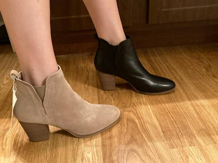 Reviewer wearing the boots in two different colors: one tan suede and one black leather