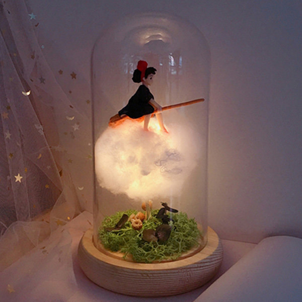 a glass dome light with a fake cloud and realistic grass with kiki on her broomstick on top of the cloud