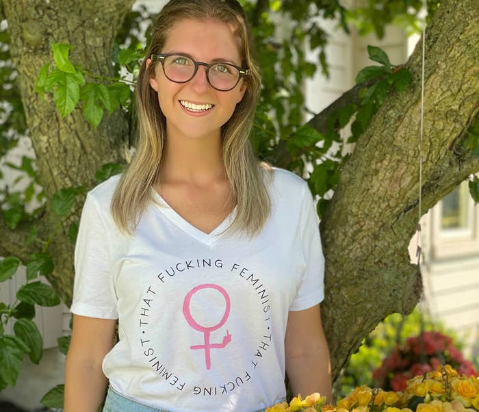 """A woman in glasses smiles while wearing a shirt that reads """"That fucking feminist."""""""
