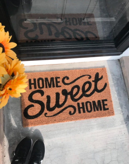 """reviewer pic of feet in sneakers looking down at doormat that says """"Home Sweet Home"""""""