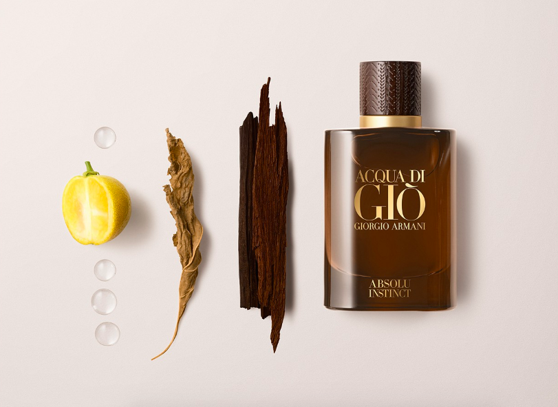 Cologne bottle beside lemon and herbs