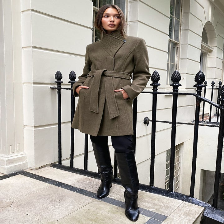 model wearing a green belted coat