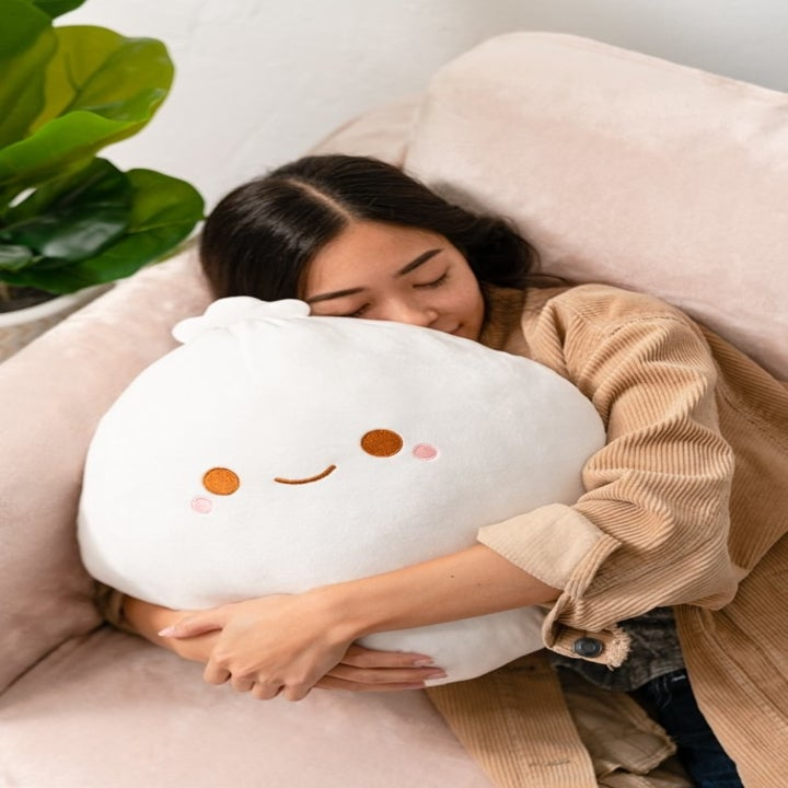 a model hugging a big plush dumpling