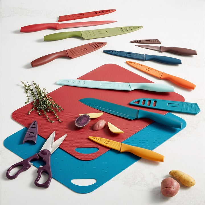 two cutting boards, a pair of scissors, and nine knives with covers, all matte and colorful