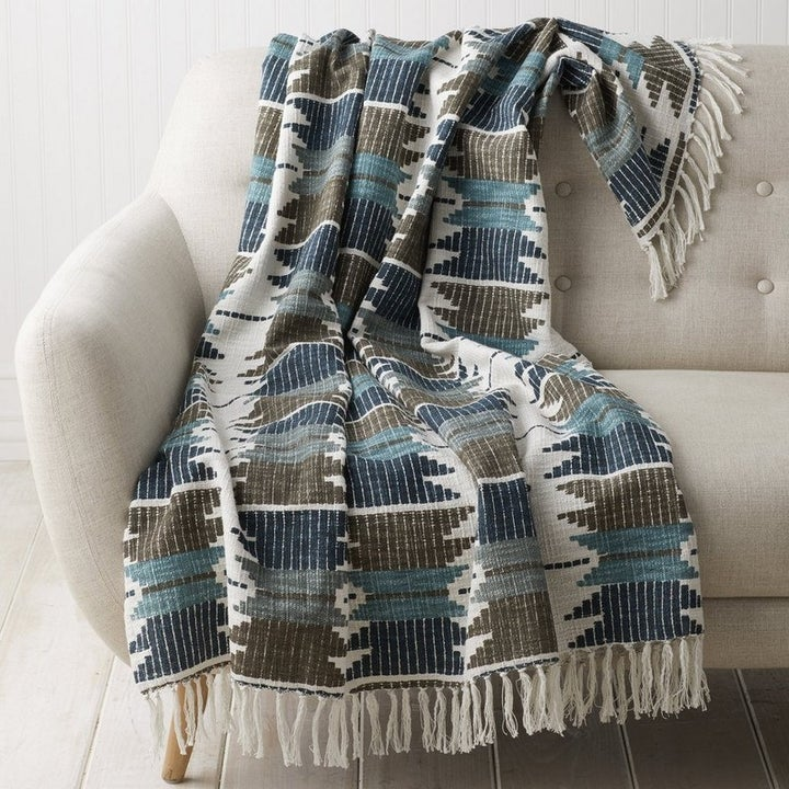a jacquard throw blanket in shades of blue and brown and tan