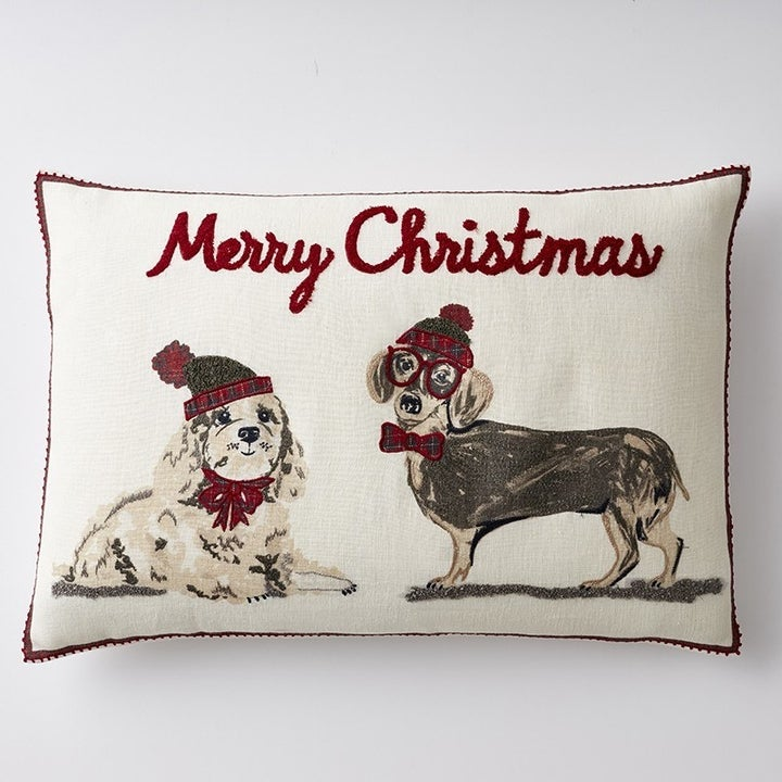 a throw pillow with two dogs wearing winter hats on them