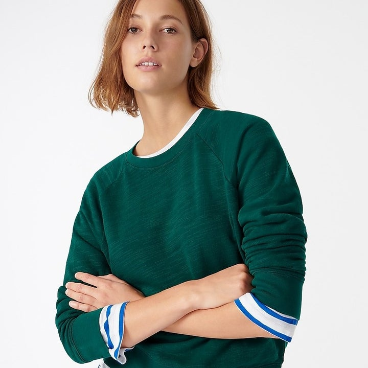 model wearing green crewneck sweater