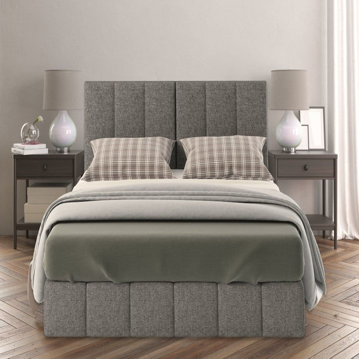 a bed with a gray plush headboard