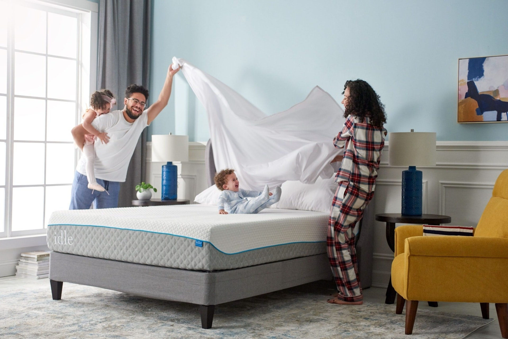 a family laughing while making their bed