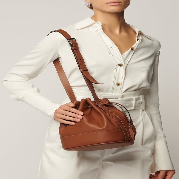 model wearing a brown leather bucket bag