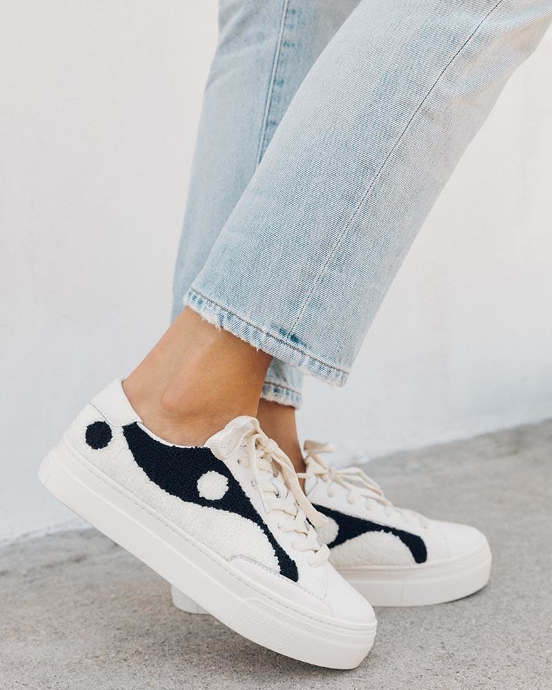 model wearing the white and black Ying Yang sneakers