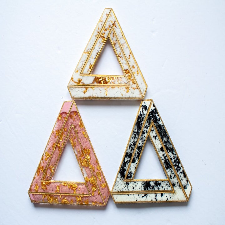 triangular coasters with gold flakes in orange, white, and black