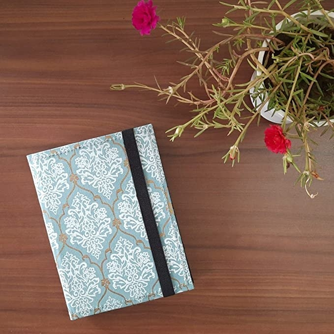 Light blue cover with a white, Jaipur style print on it.