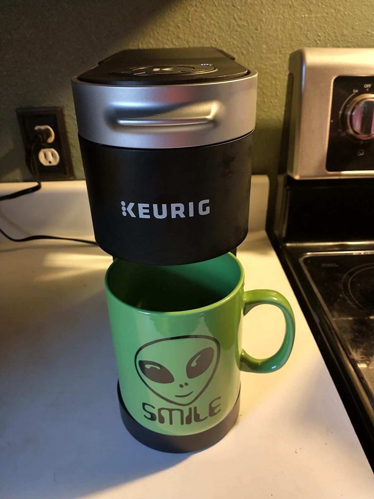 a reviewer's slim coffee machine with a green mug with an alien on it