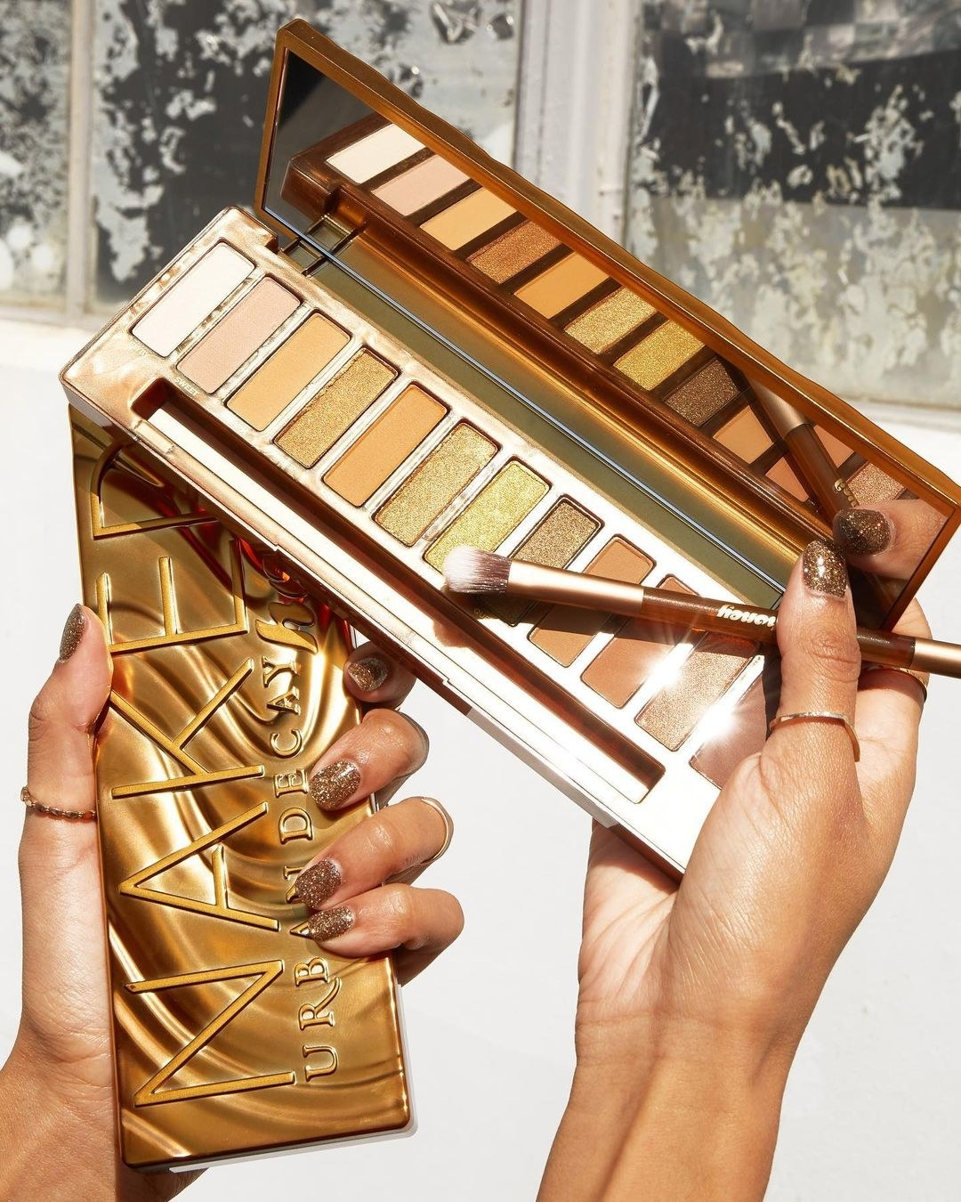 A model holding the palette, which has 12 shades of yellows and browns