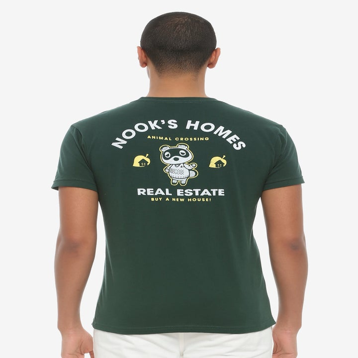 "a model showing the back of the green tee with tom nook on it and ""nook's home real estate"" written on it"