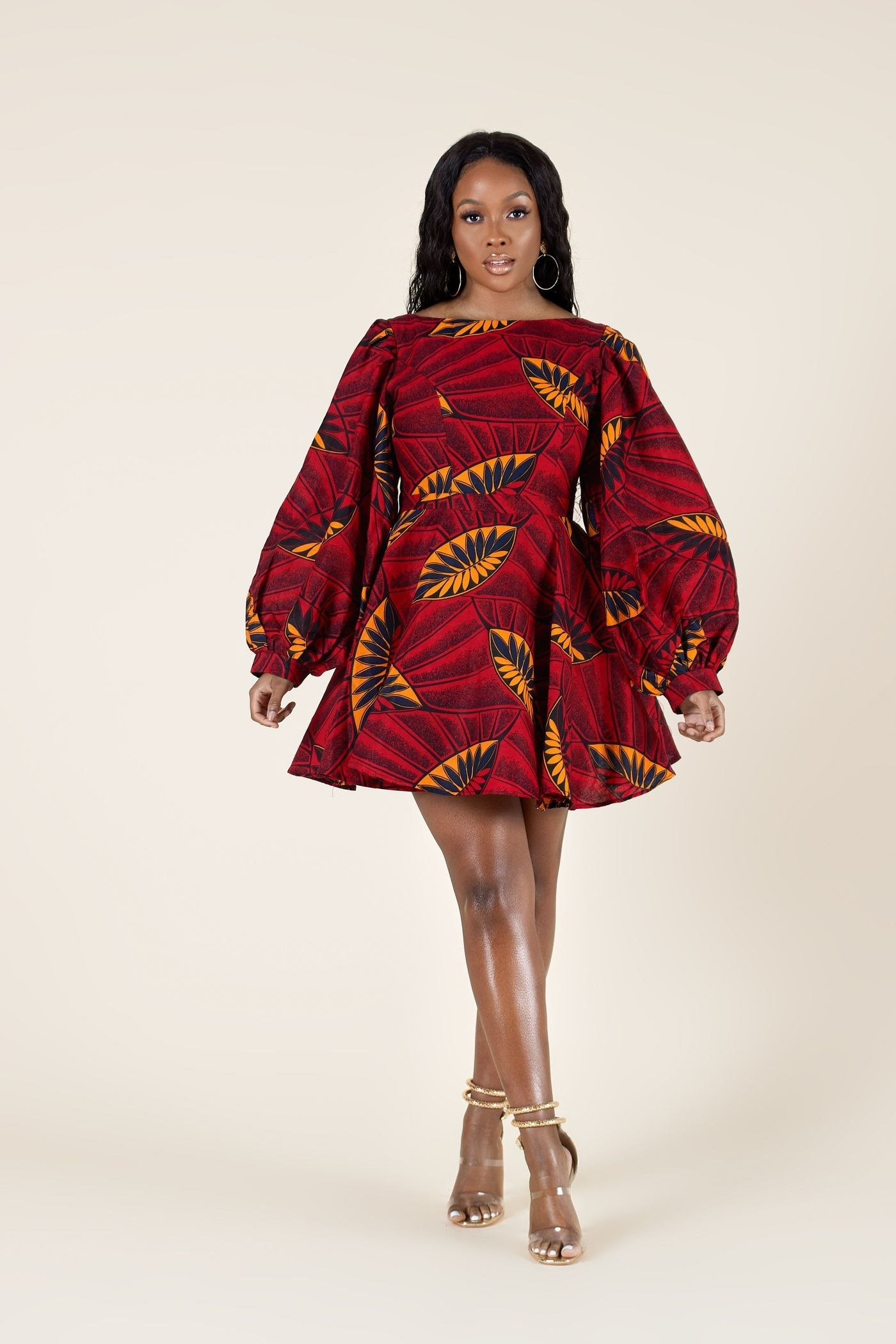 model wearing a short A-line dress with bell sleeves in a red, orange, and black Ankara print