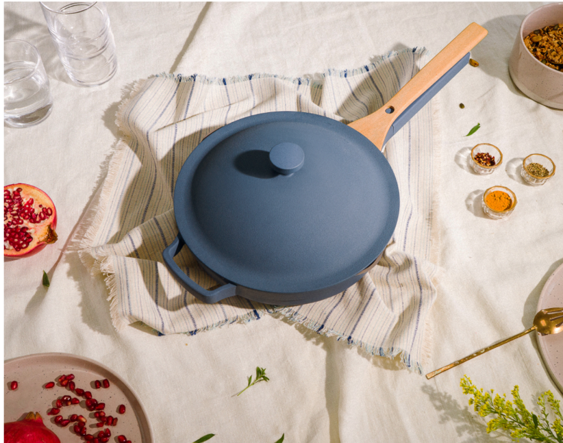 blue pan with beechwood spoon that fits neatly on handle half under the lid