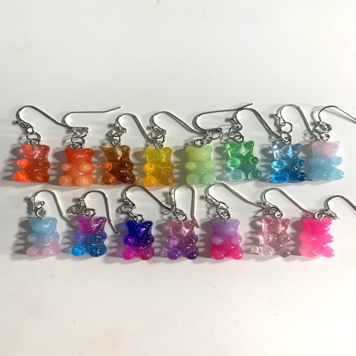 two lines of earrings that look exactly like real gummy bears in all colors of the rainbow