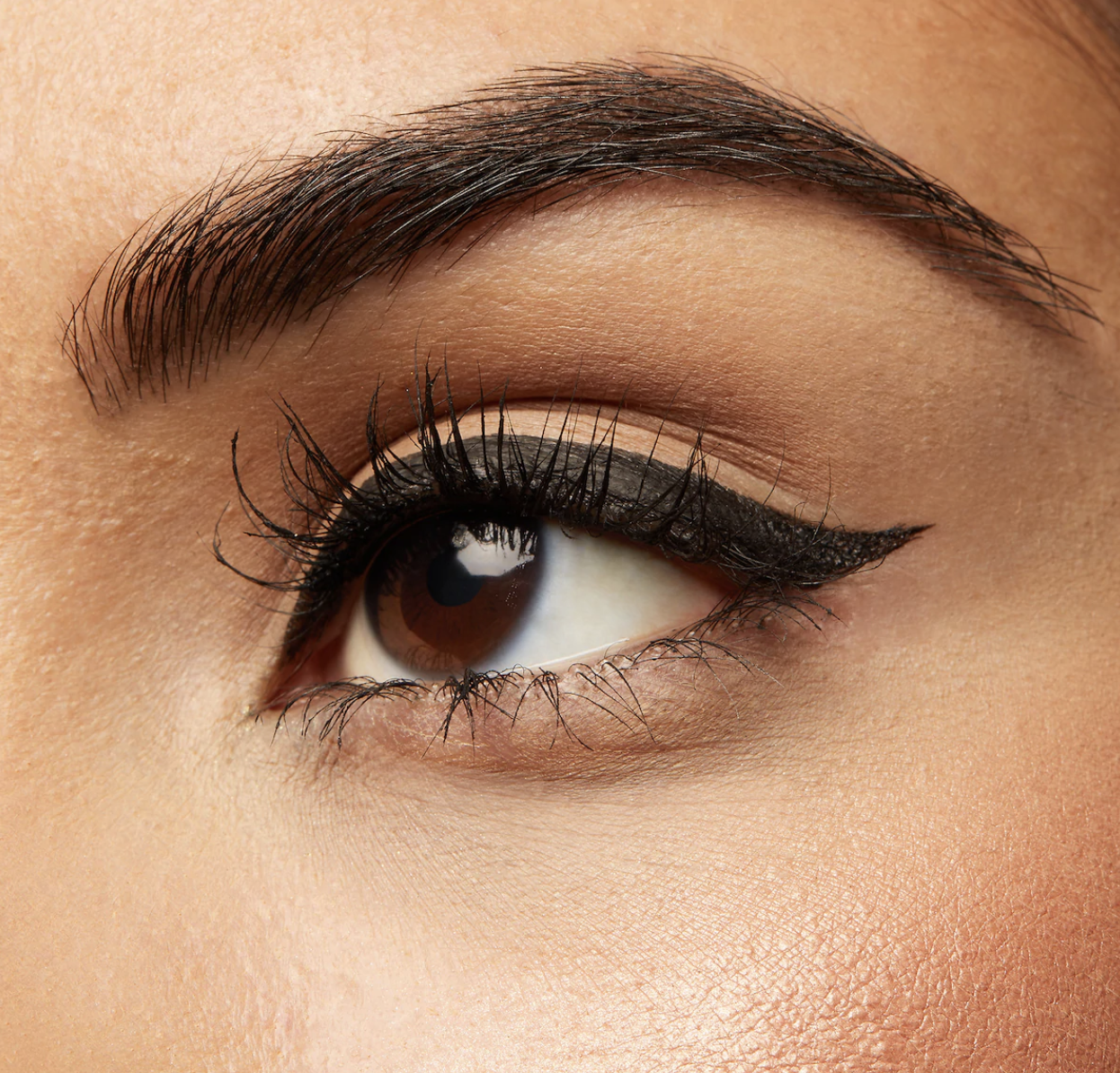 A model's eye with a winged eyeliner look and lashes looking long and slightly curled