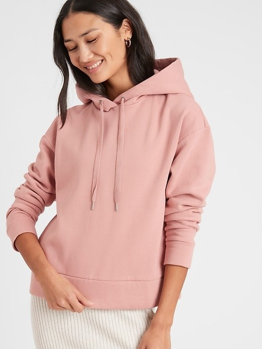 A model wearing the fleece hoodie sweatshirt in pink