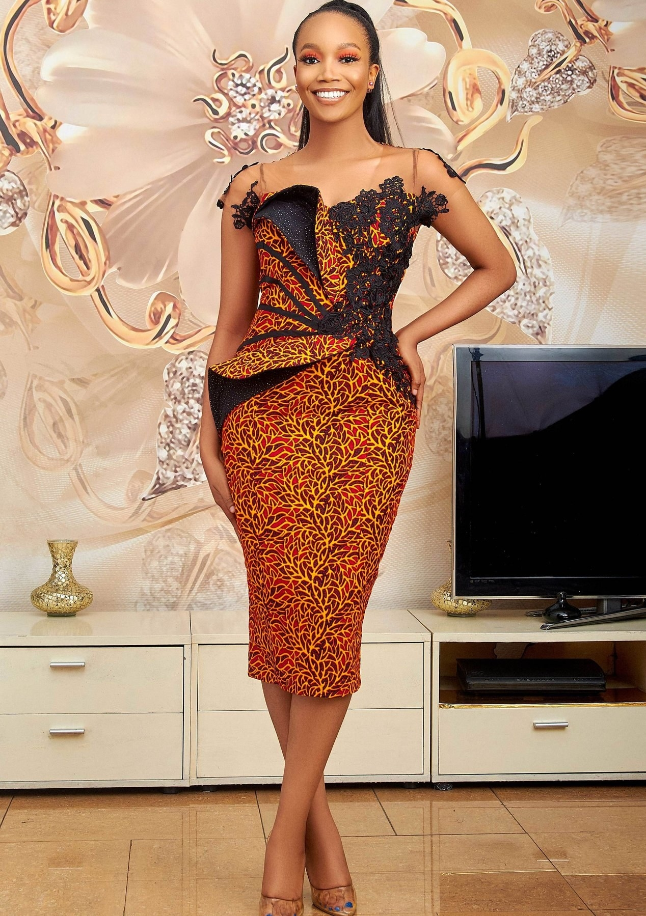 model wearing a red and dark orange leafy Ankara print dress with black lace at the top