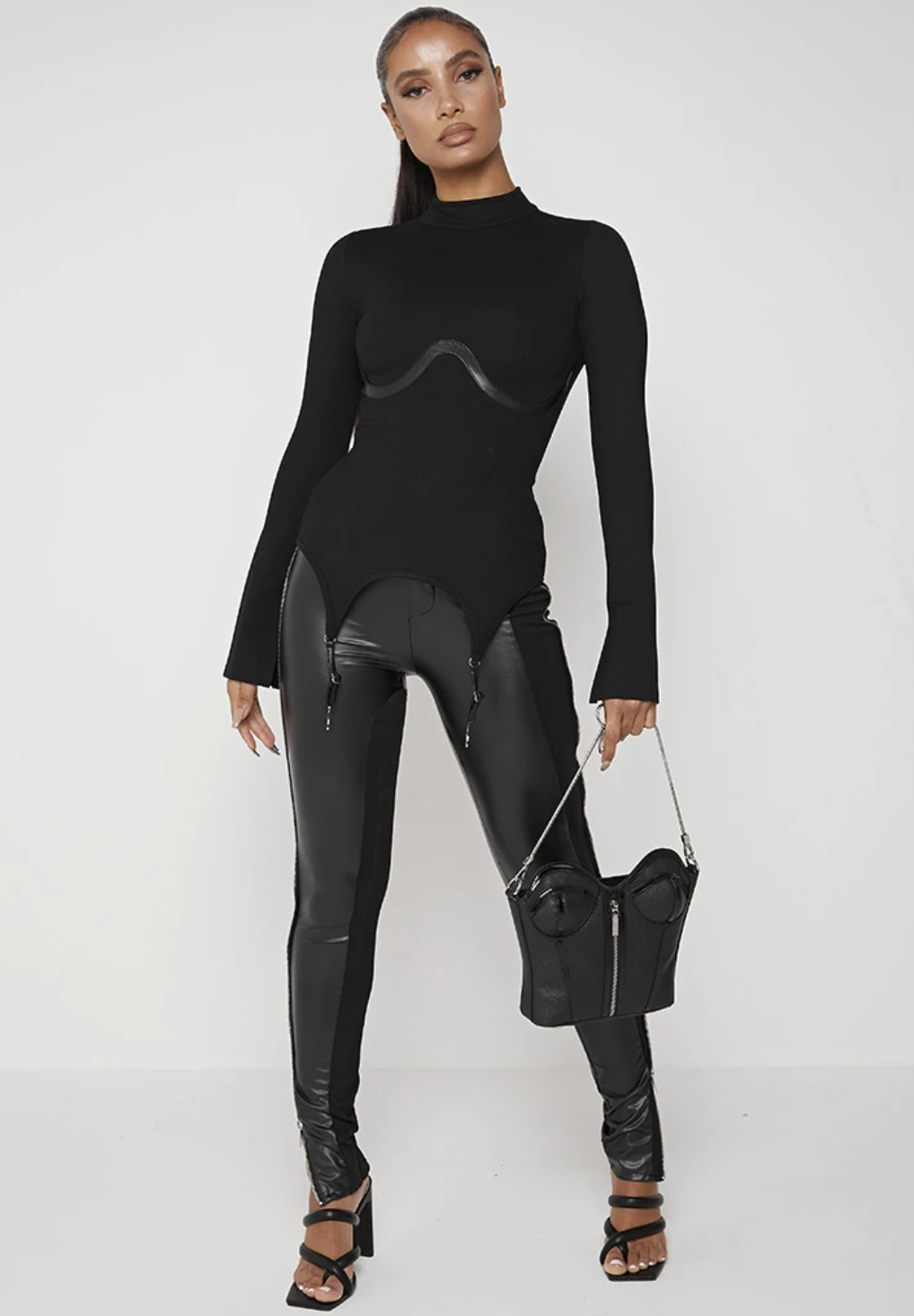 model wearing a turtleneck sweater with a corseted design, black leather pants, and a corset-shaped purse