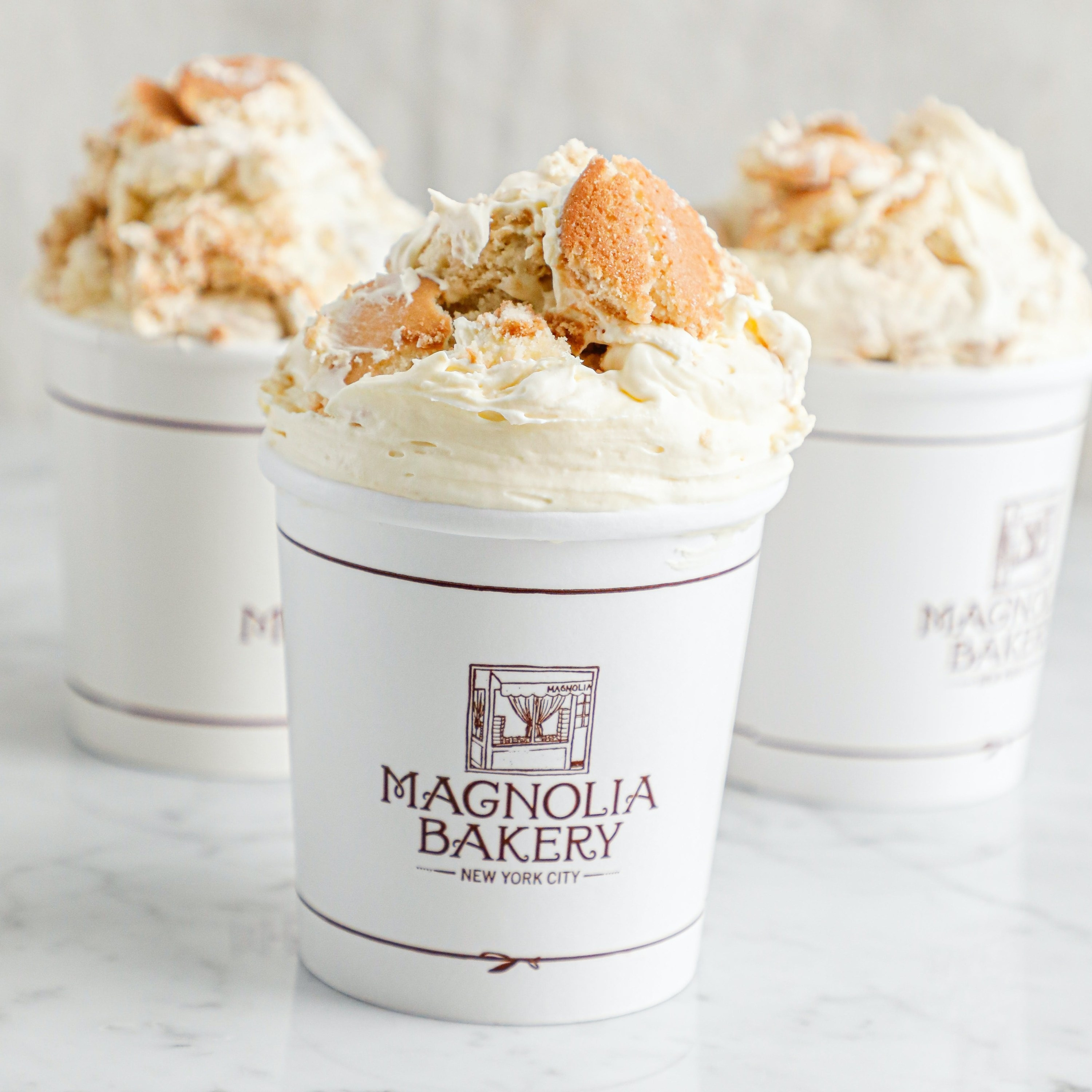 three cups of banana pudding that say magnolia bakery on the front